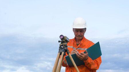 skilled surveyor fixes dumpy level on brown wooden tripod