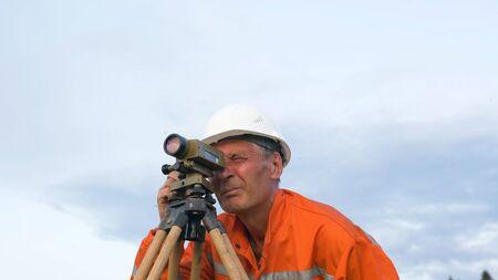professional surveyor puts brown wooden tripod on ground