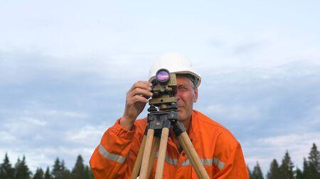 skilled surveyor in orange jumpsuit works with dumpy level