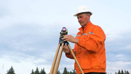 explorer in orange types on smartphone by geodetic device Stockfoto