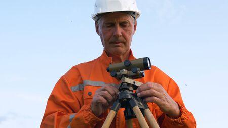 skilled surveyor in orange jumpsuit and helmet at theodolite