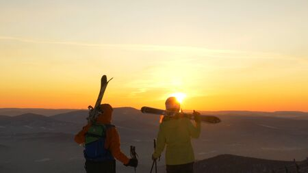 A couple of mountain skiers in love stands on the slope of the mountain and admires the sunset