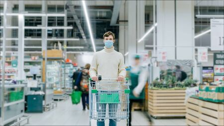 A man in a medical mask stands in a supermarket with a food cart Stockfoto