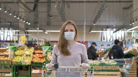 Woman in a medical mask and rubber gloves stands with a grocery cart in a supermarket against the background of shelves with goods and customers. Protection from the coronavirus pandemic. Purchase of products for quarantine.