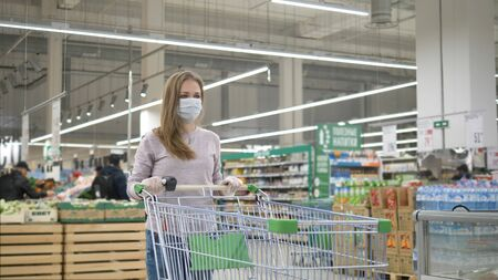 A sad woman in a medical mask and rubber gloves stands in a supermarket with a grocery cart and looks ahead. Personal protective equipment against coronavirus. A worldwide pandemic covid-19.