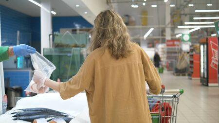 A young girl in a supermarket in a medical mask and gloves buys fish. The seller passes a bag of fish in gloves. Precautions against coronavirus infection. Stockfoto