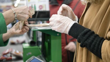 Woman at the supermarket checkout picks up change after shopping in rubber protective gloves. Safety measures against coronavirus infection.