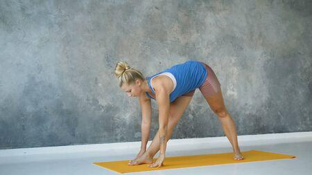 girl practices yoga in light studio on yellow mat