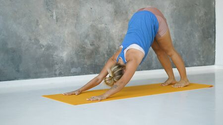 Beautiful blond girl is doing on the Mat yoga, Surya Namaskar downward dog, exercise fitness workout