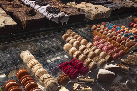 Fresh delicious sweet cakes are in the store behind a glass window
