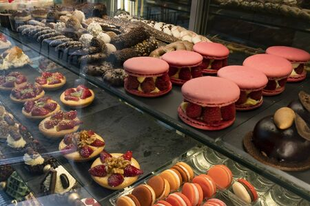 A variety of sweet delicious cakes on the window of the cafe attract a sweet tooth
