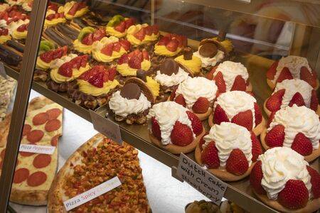 Fresh delicious sweet cakes with strawberries are in the store behind a glass window