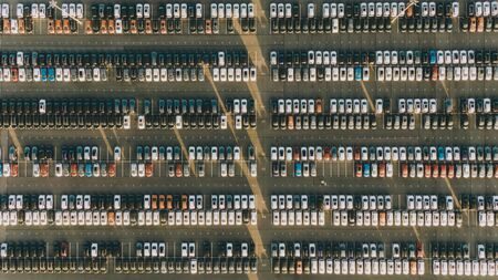 New cars stand in even rows in the territory of an automobile plant, aerial view. The economic crisis of overproduction, mass production, lack of demand. 版權商用圖片