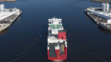 A giant tanker with fuel comes into the seaport, aerial view. Hydrocarbon fuel transportation by sea. Oil industry.
