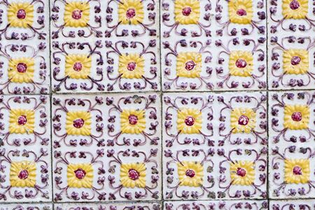 Traditional old bright tiles on old houses in Portugal, beautiful yellow flowers Stock Photo