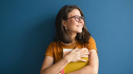 Beautiful woman designer in glasses smiling and looking at the camera holding a stack of papers in his hands on a blue background, happy to perform a complex project, met the deadline. Archivio Fotografico - 150121900