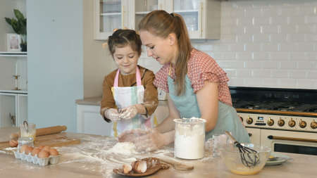 Cute little daughter and young mother make heap with fresh flour cooking cake at wooden table in contemporary light kitchen Standard-Bild
