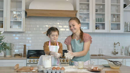 Funny little daughter and young mother have fun making dough for tasty pie at large wooden table in contemporary kitchen