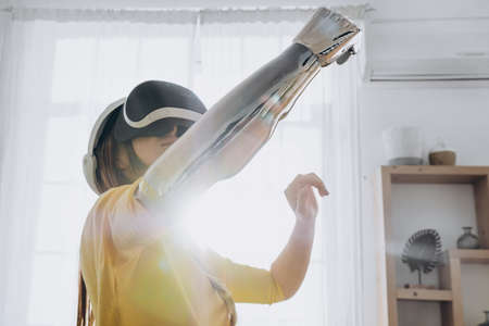 A young woman with a bionic hand in virtual reality glasses has her hands up and touches the air of the house in a yellow blouse in front of the window in a bright room.