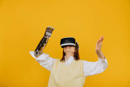 Smiling person with bionic arm and VR headset on yellow