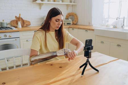 Concentrated woman controls bionic arm using smartwatch Reklamní fotografie
