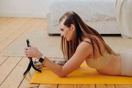 Sportive woman with shiny prosthesis uses phone on floor Reklamní fotografie