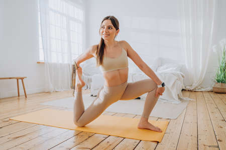 Attractive lady with bionic prosthesis does yoga exercises