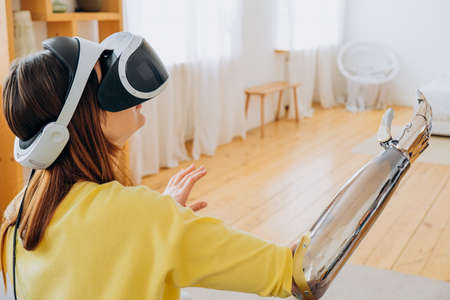 Woman with bionic arm and VR headset plays game in room