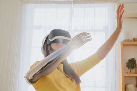Happy woman with bionic arm and virtual reality goggles Reklamní fotografie