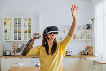 Lady with bionic arm and virtual reality goggles in kitchen