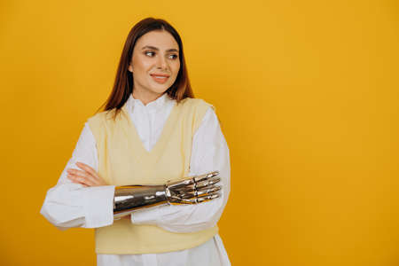 Woman with bionic prosthesis crosses arms by yellow wall