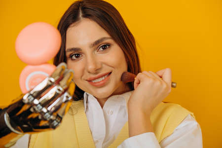 Attractive woman with bionic arm applies makeup on yellow Reklamní fotografie