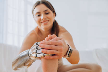 Cheerful woman with bionic arm does stretching exercises