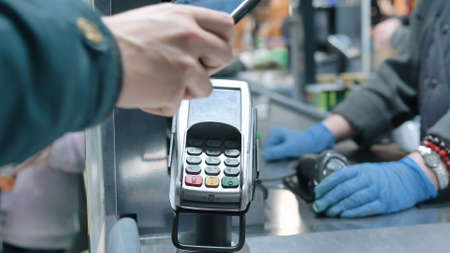 Man hand holds smartphone and pays bringing to terminal