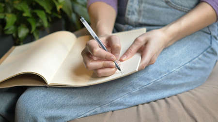 Young student holds copybook on knees and writes notes