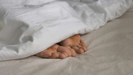 Sleepy person covered with blanket wriggles toes in bed