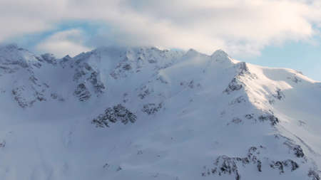Old mountains with snowy peaks under blue sky with clouds Reklamní fotografie