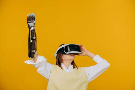 Woman in vest with bionic arm and VR headset plays game