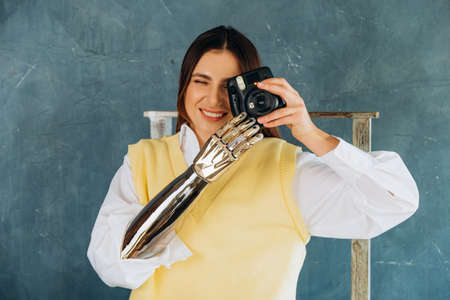 Young woman with metal bionic arm takes picture on grey