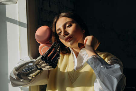 Attractive woman with a bionic prosthetic arm applies makeup with a brush standing at the window and looks in a small mirror