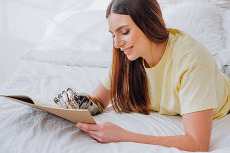 Woman writes in paper notebook with bionic arm lying on bed