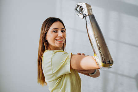 Portrait of a strong and independent woman with a bionic prosthetic arm shows a bicep on a light background
