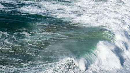 Giant ocean waves crash on the water surface forming a rainbow