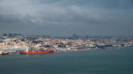 Gigantic ship stands at the pier of the Lisbon seaport and the view of the city from the sea