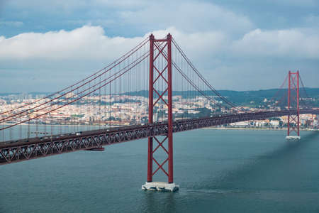 Modern bridge on April 25 in Lisbon in cloudy cloudy weather