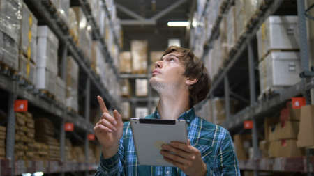 man looks at shelves and enters goods information to tablet