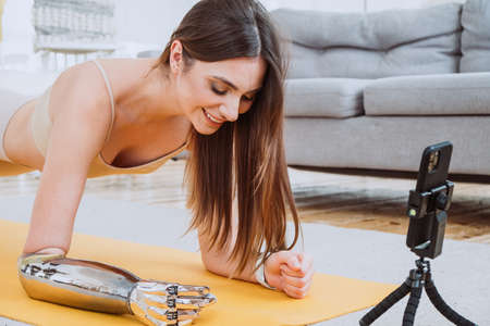 Happy woman with prosthesis arm does yoga near phone in room