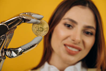 Lady with shiny bionic arm holds golden bitcoin on yellow