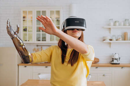 Woman with bionic arm and VR headset dances in kitchen