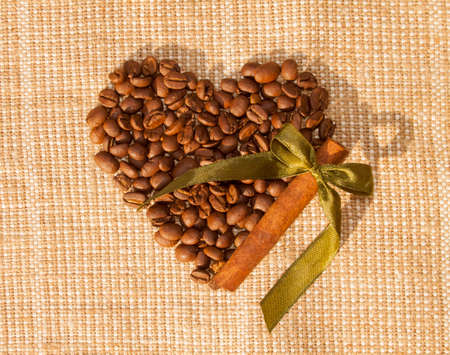 bens: Heart shape coffee bens with cinnamon stick on a background of burlap.